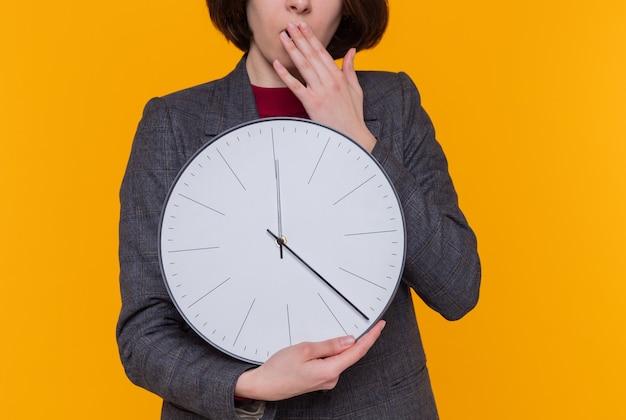 Giovane donna con i capelli corti che indossa giacca grigia che tiene orologio da parete guardando stupito e sorpreso che copre la bocca con la mano in piedi sopra la parete arancione
