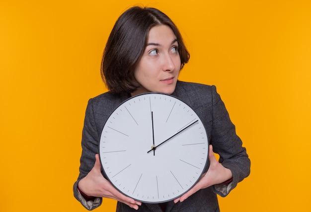 Giovane donna con i capelli corti che indossa giacca grigia che tiene l'orologio da parete che osserva da parte con un'espressione sospettosa che sta sopra la parete arancione