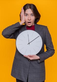 Giovane donna con i capelli corti che indossa giacca grigia che tiene orologio da parete guardando davanti stupito e sorpreso in piedi sopra la parete arancione