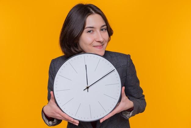 Giovane donna con i capelli corti che indossa giacca grigia che tiene orologio da parete guardando davanti sorridendo allegramente felice e positivo in piedi sopra la parete arancione
