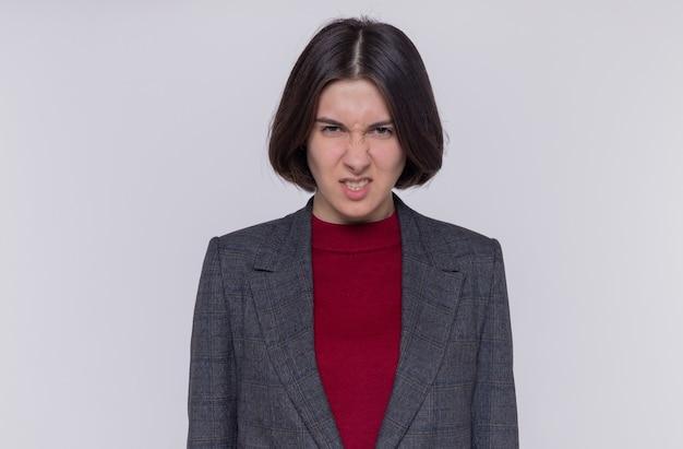 카메라를보고 회색 재킷을 입고 짧은 머리를 가진 젊은 여자