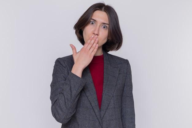 白い壁の上に立っている手で口を覆ってショックを受けている正面を見て灰色のジャケットを着て短い髪の若い女性