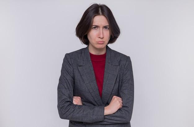 회색 재킷을 입고 짧은 머리를 가진 젊은 여자는 찡그린 얼굴이 팔로 불쾌한 얼굴을 앞에보고 흰 벽 위에 서 교차