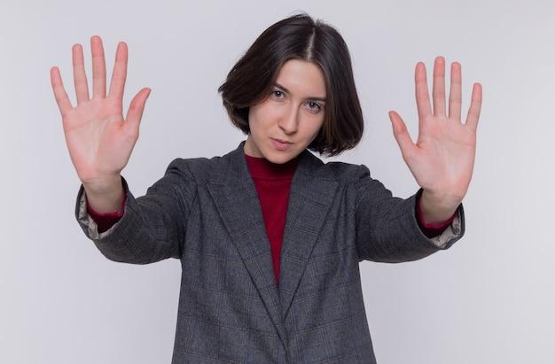 Молодая женщина с короткими волосами, одетая в серый пиджак, смотрит вперед с серьезным лицом, делая жест стоп с руками, стоящими над белой стеной