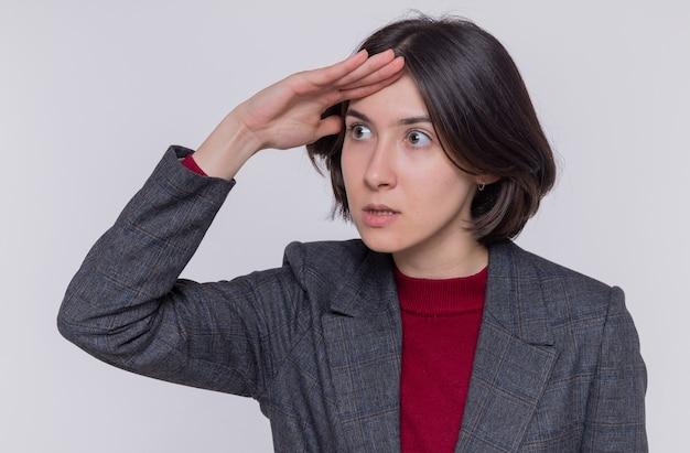 灰色のジャケットを着た短い髪の若い女性
