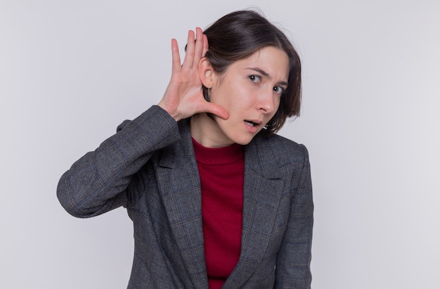 白い壁の上に立って耳を傾けようとしている彼女の耳に手をつないで興味をそそられるように見える灰色のジャケットを着ている短い髪の若い女性