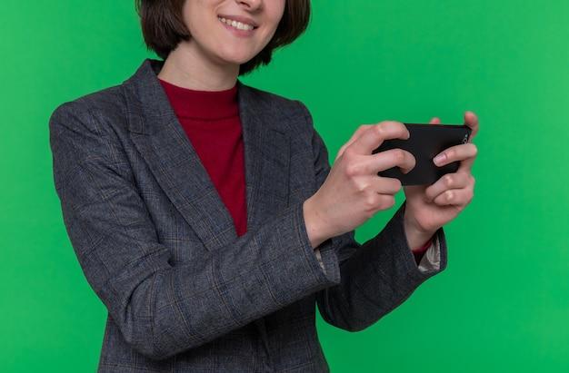 Молодая женщина с короткими волосами в серой куртке играет в игры с помощью смартфона, счастливая и веселая стоя над зеленой стеной