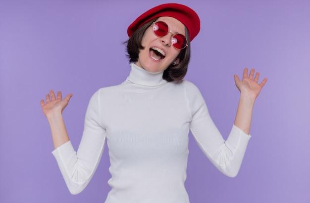 Giovane donna con i capelli corti in dolcevita bianco che indossa berretto e occhiali da sole rossi felice ed eccitato urlando gioia alzando le mani in piedi sopra la parete blu