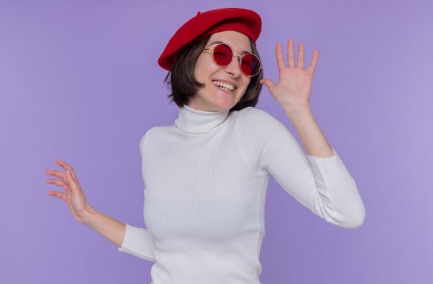 Giovane donna con i capelli corti in dolcevita bianco che indossa berretto e occhiali da sole rossi felice ed eccitato sorridendo allegramente gesticolando con le mani in piedi sopra la parete blu