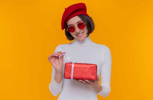 Young woman with short hair in white turtleneck wearing beret and red sunglasses holding a present happy and cheerful going to open present smiling cheerfully