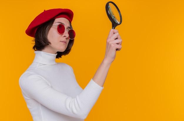 Giovane donna con i capelli corti in dolcevita bianco che indossa berretto e occhiali da sole rossi guardando da parte attraverso questa lente di ingrandimento con faccia seria in piedi sopra la parete arancione