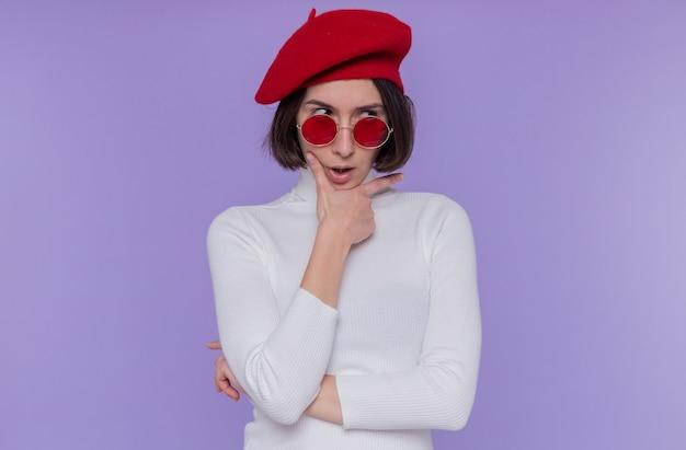 Giovane donna con i capelli corti in dolcevita bianco che indossa berretto e occhiali da sole rossi che osserva da parte con espressione scettica pensando in piedi sopra la parete blu