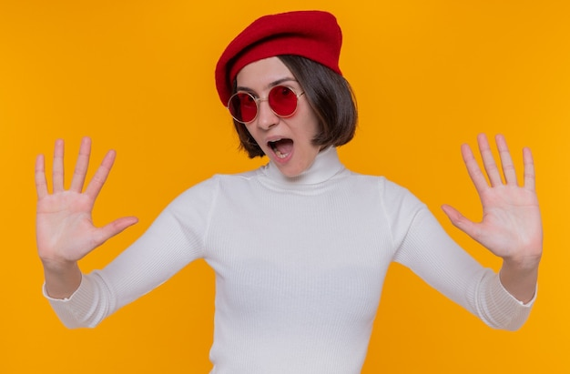 Giovane donna con i capelli corti in dolcevita bianco che indossa berretto e occhiali da sole rossi guardando davanti urlando essendo eccitato mostrando il gesto di arresto con le mani in piedi sopra la parete arancione