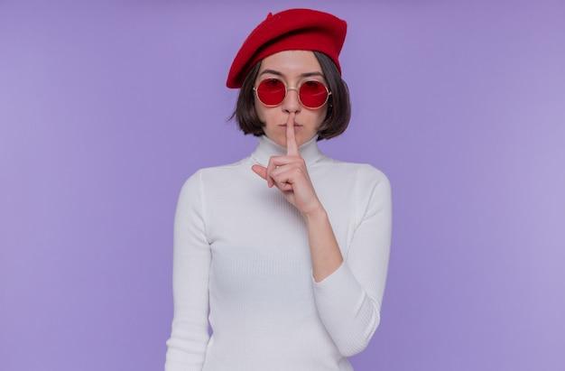 Giovane donna con i capelli corti in dolcevita bianco che indossa berretto e occhiali da sole rossi guardando davanti con faccia seria che fa gesto di silenzio con il dito sulle labbra in piedi sopra la parete blu