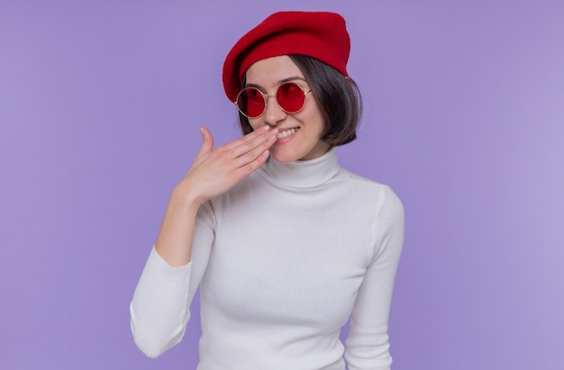 Giovane donna con i capelli corti in dolcevita bianco che indossa berretto e occhiali da sole rossi che sembrano felici