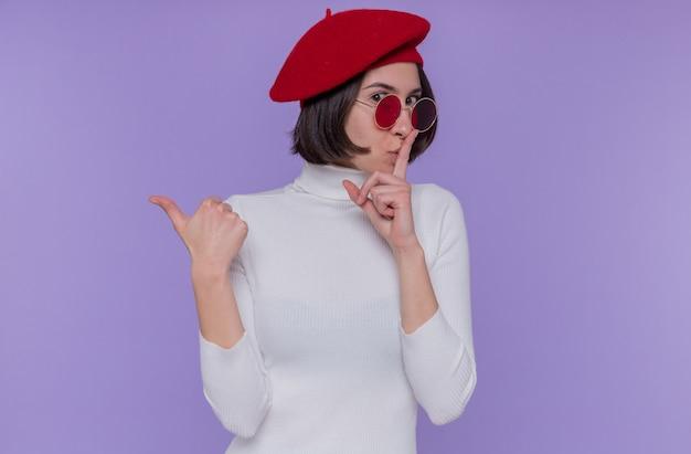 Giovane donna con i capelli corti in dolcevita bianco che indossa berretto e occhiali da sole rossi che fa il gesto di silenzio con il dito sulle labbra che punta indietro con il pollice guardando davanti in piedi sopra la parete blu