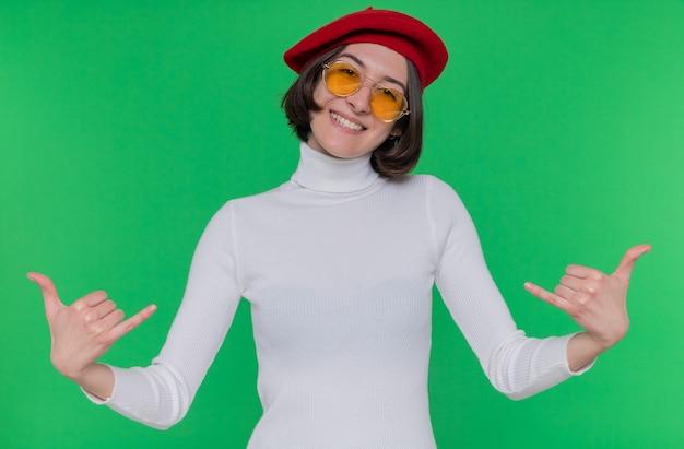Giovane donna con i capelli corti in dolcevita bianco che indossa berretto e occhiali da sole gialli guardando davanti sorridente felice e positivo che mostra allegramente chiamami gesto in piedi sopra la parete verde