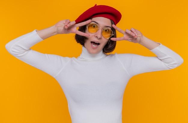 Giovane donna con i capelli corti in dolcevita bianco che indossa berretto e occhiali da sole gialli guardando davanti sorridendo allegramente mostrando v-segno in piedi sopra la parete arancione