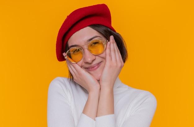 Giovane donna con i capelli corti in dolcevita bianco che indossa berretto e occhiali da sole gialli
