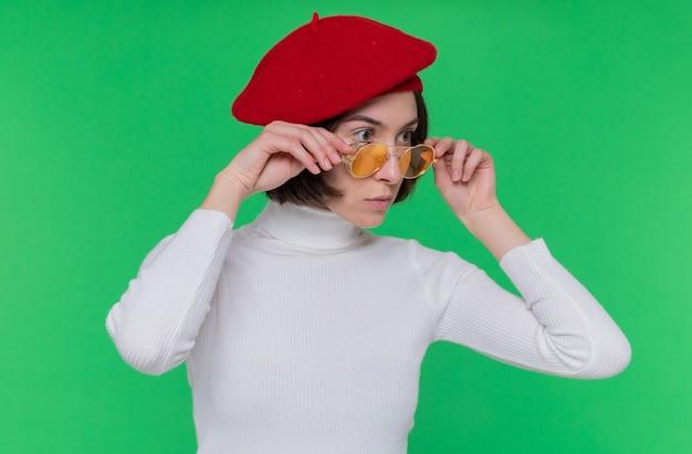 Giovane donna con i capelli corti in dolcevita bianco che indossa berretto