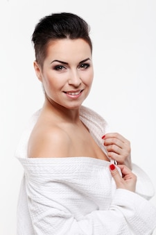 Young woman with short haircut in bathrobe