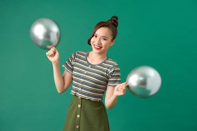 緑の上の銀の風船を持つ若い女性