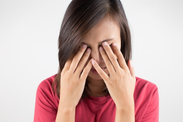 Young woman with sinus pressure pain against gray background