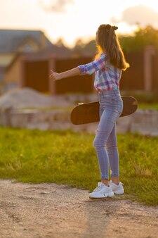 Молодая женщина со скейтбордом едет на обочине сельской дороги в теплом свете заходящего солнца