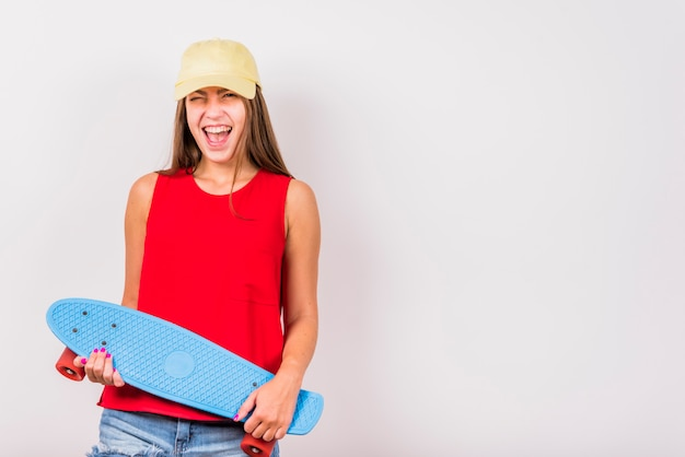 Young woman with skateboard laughing on white background