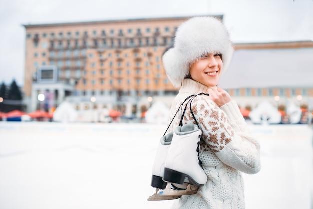 Молодая женщина с коньками в руках на катке. зимнее катание на коньках на свежем воздухе, активный отдых