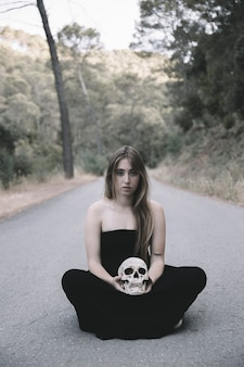 Young woman with skull sitting on road