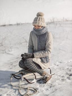 Молодая женщина с санями, одетая в повседневную зимнюю одежду. женщина страдает холодной зимой на открытом воздухе.