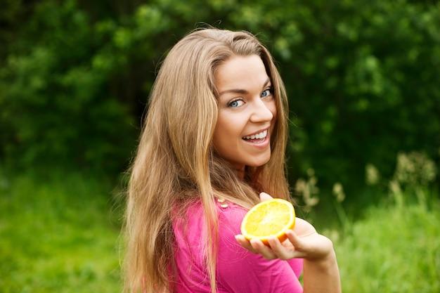 オレンジのスライスを持つ若い女性