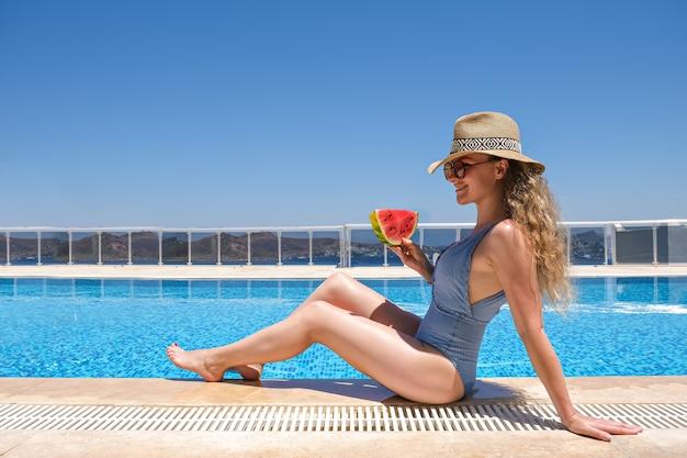 Молодая женщина с ломтиком арбуза в соломенной шляпе, загорая на краю бассейна