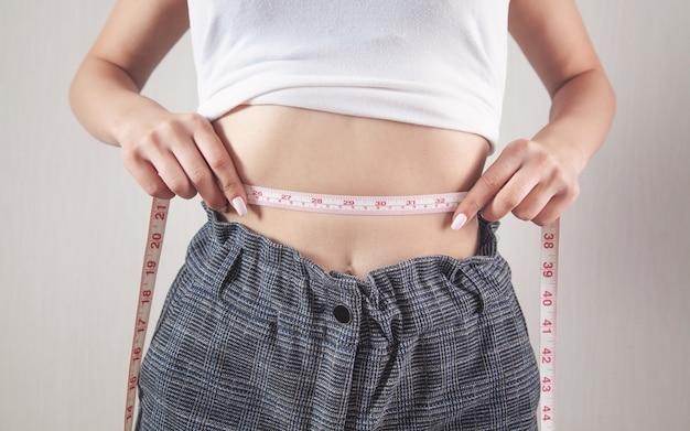 그녀의 허리를 측정하는 슬림 시체와 함께 젊은 여성. 체중 감소, 다이어트, 가정 훈련
