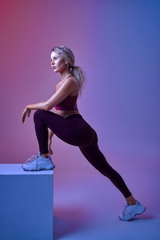 Young woman with slim body poses at cube in studio, neon background, perfect stretching. sportswoman at the photo shoot, sport concept, active lifestyle motivation