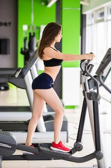 Young woman with slim fitness body works on elliptical trainer alone in sportclub