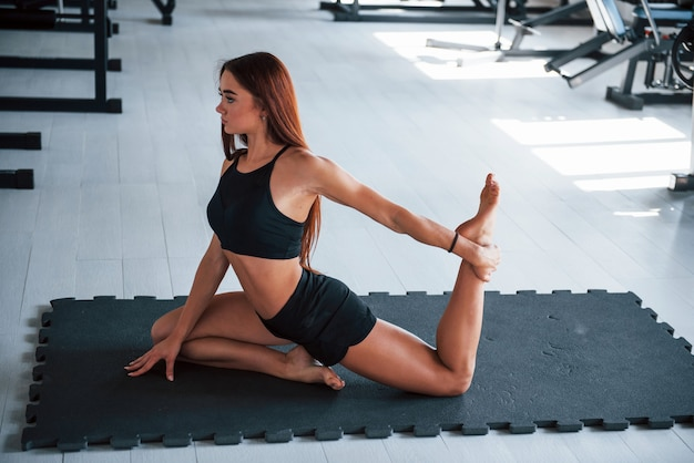 Young woman with slim type of body and in black sportive clothes doing yoga on the fitness mat.