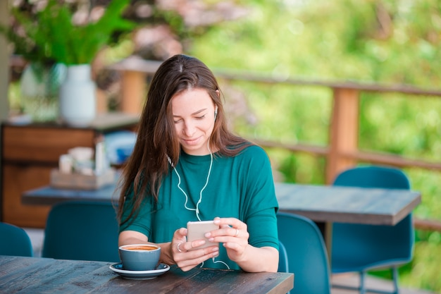Young woman with smart phone while sitting alone in coffee shop during free time