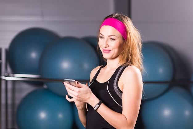 체육관에서 스마트 폰 및 피트니스 추적기를 가진 젊은 여자, 운동 휴식
