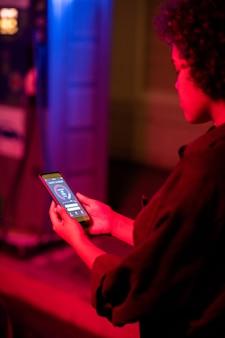 Молодая женщина с смартфоном, проверяющим уровень заряда ev