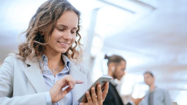 地下鉄の駅でスマートフォンを持つ若い女性