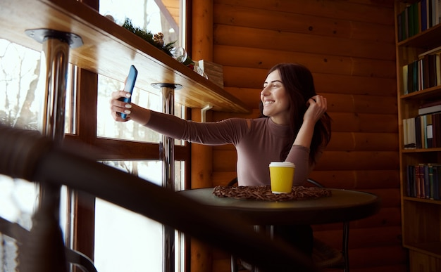 Young woman with smartphone and paper cup of tasty coffee smiles while making selfie sitting at the cafe on the background of a wooden wall and shelves with books