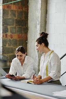 Молодая женщина со смартфоном просматривает онлайн-тенденции моды, в то время как ее коллега с блокнотом и ручкой делает заметки