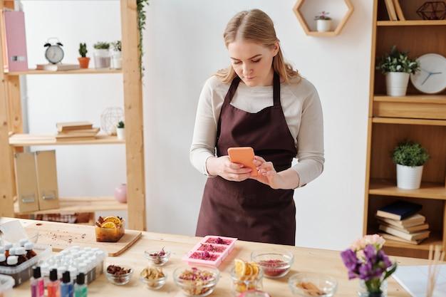 スタジオで木製のテーブルにシリコーン型の手作り石鹸の写真を撮るスマートフォンを持つ若い女性