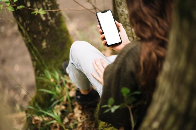 Giovane donna con il modello di smartphone in natura