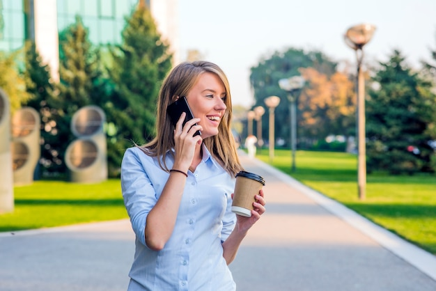 Young woman with smartphone walking on street, downtown. in background is blurred street, looking in front