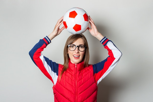 Young woman with a smile in a red vest holds a soccer ball above her head against a light wall