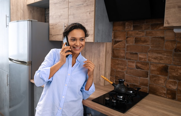 The young woman with a smile speaks on the phone while standing in the kitchen.
