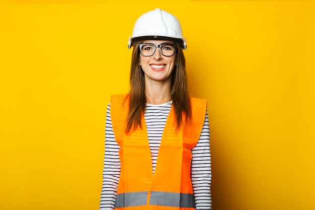 Young woman with a smile in a vest and hard hat on yellow
